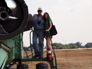 Bruce & Hilary climbing down from the Moose after dumping the last load of wheat (grain-cart auger on the left).